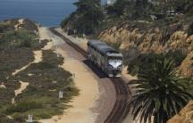 An Amtrak passenger train makes its way along the coastline