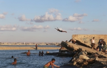 A beachgoer dives into the waters of the Mediterranean Sea, off the coast of Benghazi, Libya