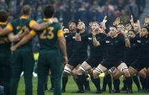 Men in black uniforms facing each other doing dance