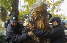 Policemen detain a person dressed as Star Wars character Chewbacca during a regional election near a polling station in Odessa, Ukraine, October 25, 2015.