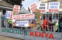 Protesting Kenyan athletes place placards behind closed gates at Riadha House the Athletic Kenya (AK) Headquarters in capital Nairobi November 23, 2015.