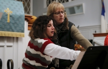 A woman and young girl in a church look at sheet music