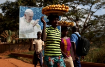 Women carrying fruits and vegetables on their heads walk past a billboard with a photograph of Pope Francis, in Bangui, Central African Republic; November 26, 2015.