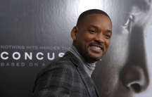 """Actor Will Smith poses as he arrives for the New York premiere of the film """"Concussion"""" in the Manhattan borough of New York City, December 16, 2015. """"Concussion"""", which stars Smith portraying Dr. Bennet Omalu, the pathologist who a decade ago first linke"""