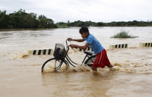 A boy pushes his bike through a flooded road after heavy rain in Candaba, Pampanga province, Philippines on Dec. 17, 2015.