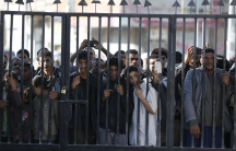 People look through a gate bars in Sanaa