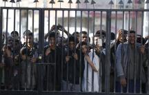 People look through a gate bars in Sanaa
