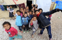 Children pose near tents inside an informal settlement for Syrian refugees in Bekaa Valley, Lebanon.