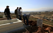 Men dig graves inside a graveyard for Syrian refugees in the village of Taalabaya, Bekaa Valley, Lebanon, Jan. 10, 2016.