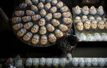 A worker puts the final touches on a carnival mask bearing the likeness of federal police agent Newton Ishii, at a costume factory in the suburb of Rio de Janeiro, Brazil, January 11, 2016.