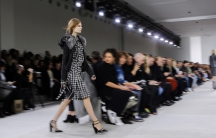 A woman walks on a catwalk around people sitting in chairs