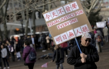 """A man holds a sign that reads """"All lives matter"""" in English and Chinese"""