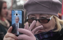 A woman holds a phone with a picture of Vladimir Putin on it.