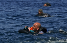 A Syrian refugee holding a baby in a life tube swims towards the shore, after their dinghy deflated some 100 yards from the Greek island of Lesbos, September 13th 2015.
