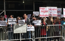 """Row of protesters behind barrier with signs that says, """"Tragic Accident doesn't equal Manslaughter."""""""