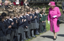 A group of British children wearing their school uniforms greet the Queen at a ceremonial opening near London