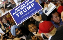 US Republican presidential candidate Donald Trump signs autographs for supporters holding a Muslim Americans for Trump sign after a rally in Harrington, Delaware April 22, 2016.