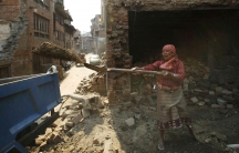 Woman with tool in front of damaged building
