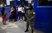 Salvadoran military police stand guard outside a school in Soyapango's La Campanera neighborhood on the outskirts of San Salvador.