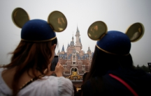 Women wearing Mickey Mouse ears watch the opening ceremony at Shanghai Disney Resort in Shanghai, China, June 16, 2016.