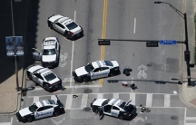Police cars remain parked with the pavement marked by spray paint, in an aerial view of the crime scene of a shooting attack in downtown Dallas.