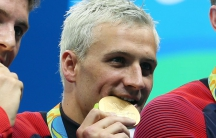 Ryan Lochte, the US swimmer, bites his Olympic gold medal in Rio de Janeiro.