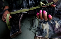 A member of the 51st Front of the Revolutionary Armed Forces of Colombia (FARC) poses for a picture at a camp in Cordillera Oriental, Colombia, Aug. 16, 2016.