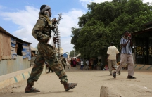 A Somali soldier patrols a street following a suicide car bomb and gun attack.