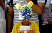 A boy in a Pikachu hat plays a Nintendo game console