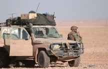 A US armed forces member stands near a military vehicle, north of Raqqa, Syria on Nov. 6.