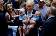Republican presidential nominee Donald Trump holds babies at a campaign rally in Colorado Springs, Colorado, U.S., July 29, 2016. REUTERS/Carlo Allegri