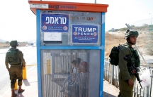 Israeli soldiers at a bus stop covered with posters from the Israeli branch of the US Republican Party, near the West Bank Jewish settlement of Ariel on Oct. 6.