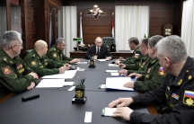 Russian President Vladimir Putin meets with military officials