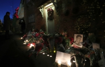 Flowers, cards and portrait of George Michael in front of brick building