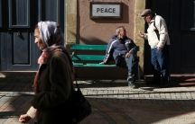 People are seen on Ledras Street next to a peace sign near the UN-controlled buffer zone in Nicosia, Cyprus, January 11, 2017.