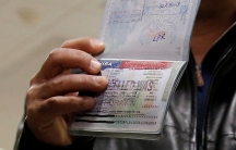 "Hand holding up passport with US visa stampend ""CANCELLED"""