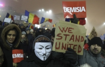 "A Romanian holds a sign that reads ""we stand united"" during a demonstration of thousands against the  government in Bucharest, Romania, Feb. 6, 2017."