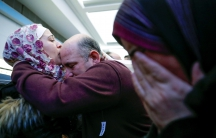 Syrian refugee Baraa Haj Khalaf (left) kisses her father Khaled as her mother Fattoum (right) cries after arriving at O'Hare International Airport in Chicago on February 7, 2017.