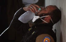 A Syrian civil defence member uses an oxygen mask after a suspected gas attack in the town of Khan Sheikhoun in rebel-held Idlib.