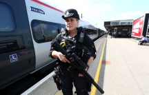 An armed police officer patrols on a platform at Milton Keynes station after the terror threat level was raised to critical following a suicide bombing in Manchester.