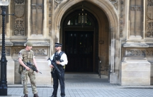 UK police and soldiers patrol outside the UK parliament in London. Britain remains at a 'Critical' level of terror alert following the bomb attack on Monday.