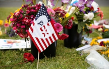 """A flag bearing an abbreviation for """"Portland"""" stands at a makeshift memorial."""