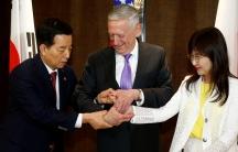South Korea's Defense Minister Han Min-koo shows US Secretary of Defense James Mattis and Japan's Defense Minister Tomomi Inada how to do a handshake