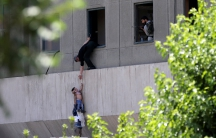 A boy is evacuated during an attack on the Iranian parliament in Tehran, Iran.
