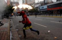 A demonstrator throws a petrol bomb during riots at a rally against Venezuelan President.