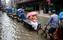 Commuters ride on rickshaws as streets are flooded due to heavy monsoon rains in Dhaka.