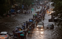 Commuters walk through water-logged roads after rains in Mumbai.