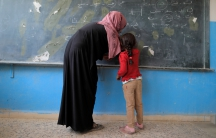 A girl attends her first class at a school in Hazema in north Raqqa, Syria.
