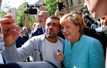 A man who identifies himself as a migrant takes a selfie with German Chancellor Angela Merkel outside a refugee camp near the Federal Office for Migration and Refugees in Berlin, Germany, Sept. 10, 2015.