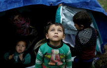 A Syrian refugee boy stands in front of his family tent at a makeshift camp for refugees and migrants next to the Moria camp on the Greek island of Lesbos, Nov. 30, 2017.